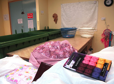 A bin full of textiles and books next to a sorting table. On the table are a blue and a white laundry basket, and behind it are two rubbish skips.