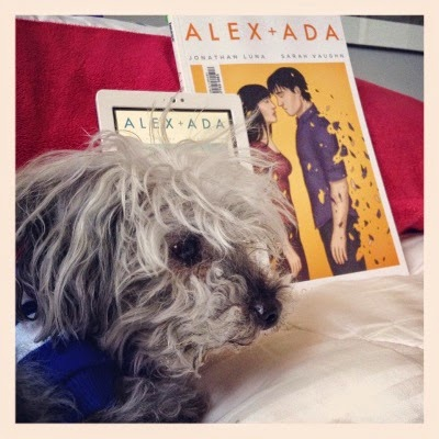 Murchie lays on a white counterpane with his front legs tucked under him. Behind him, propped against a red pillow, are a white Kobo and a trade paperback copy of Alex + Ada Volume Two. Murchie's head obscures most of the Kobo's screen. The book's cover shows two pale-skinned people seemingly about to kiss. One of them has begun to disintegrate.