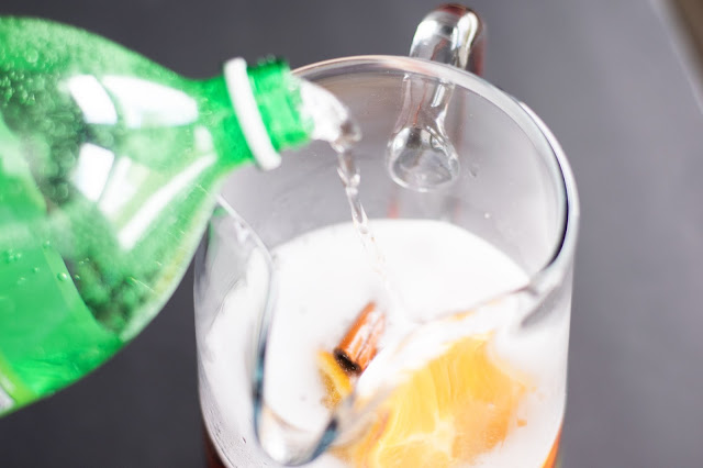 The lemon lime soda being added to the simple sangria.