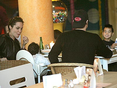 angelina jolie enjoying eating while looking at her baby