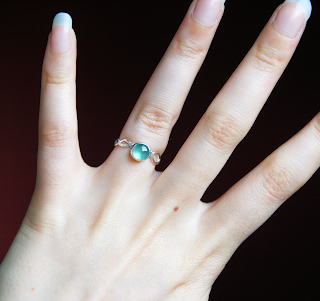Silver sea-green tourmaline wave ring being worn