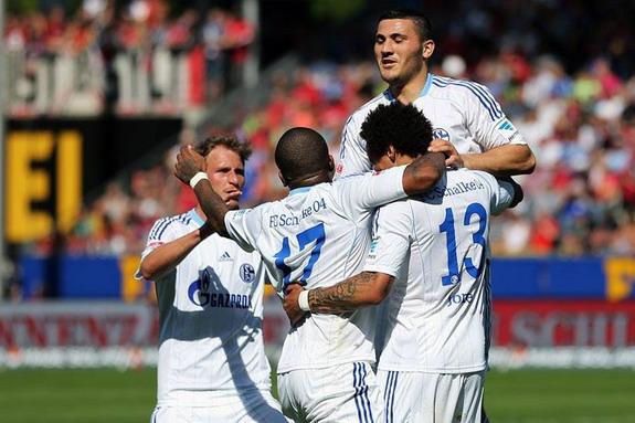 Schalke players celebrate after Freiburg midfielder Julian Schuster had scored an own goal