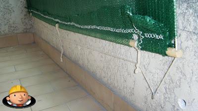 Cortinado de rede sombreira fixado no muro do gradeamento da varanda