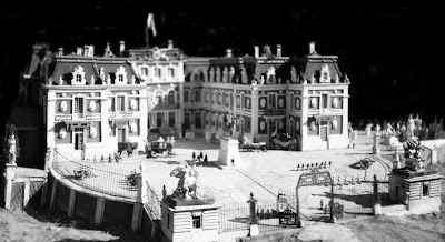 b/w image of Versailles Palace forecourt with grills, gate and guard blocks.