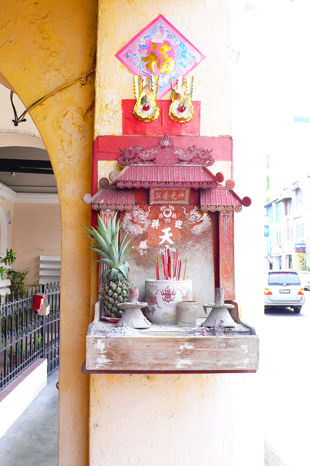 Offering shelf in Georgetown, Penang with Pineapple and josh sticks.