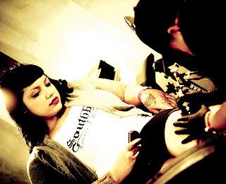 girl making tattoos on her legs