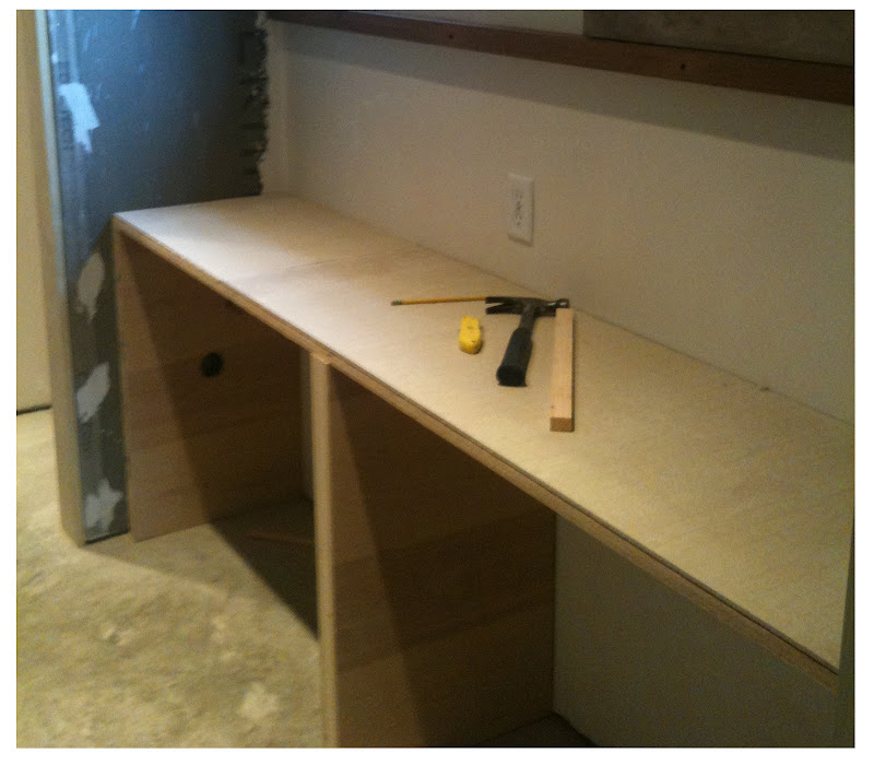 First, we built a vanity out of plywood and installed a cement  title=