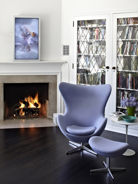 Library with dark wood floor, fireplace with white moulded mantel, a  lavender Arne Jacobsen's 1958 Egg Chair with matching foot rest, a white round side table and bookshelves with glass doors