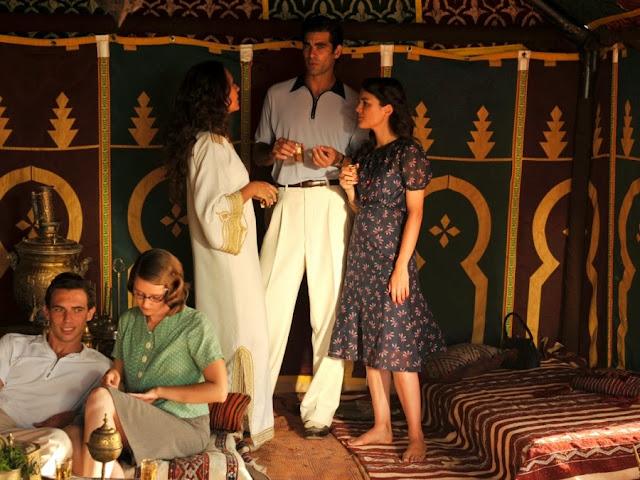 Sira Quiroga playa vestido azul con flores y Ramiro polo azul y pantalones blancos. El tiempo entre costuras. Capítulo 1.