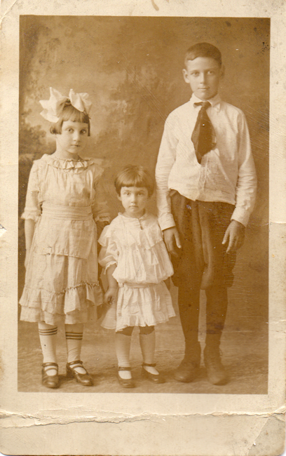Photo of two girls and a boy in early 20th Century dress