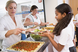 students being served lunch in cafeteria line