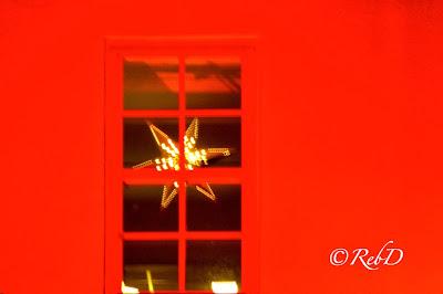 Fönster med julstjärna, i röd fasad. foto: Reb Dutius