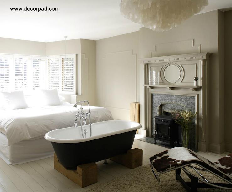 Dormitorio con bañera junto a la cama matrimonial