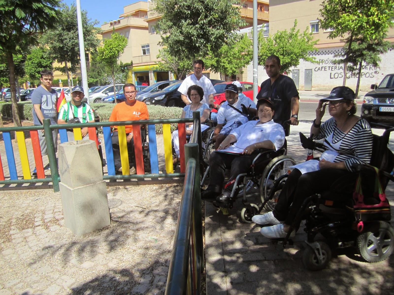 Entre los participantes y la fuente hay una valla que rodea la zona de juegos infantiles, a la que los usuarios de silla de ruedas no pueden acceder porque está pavimentada con gravilla.