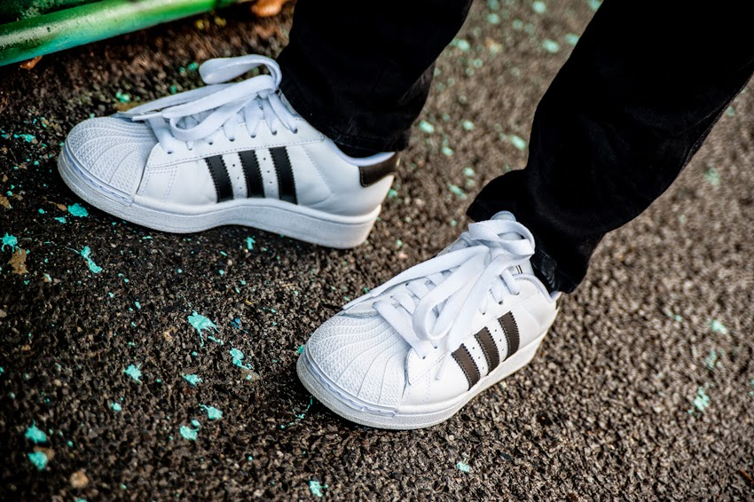 Adidas Superstar black and white sneakers side on with paint splattered foot path