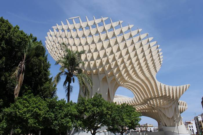 Metropol Parasol is a wooden structure located at La Encarnación square, in the old quarter of Seville, Spain. Designed by German architect Jürgen Mayer-Hermann, the structure resembles a grove of prefabricated wooden trees soaring 26 meters into the air. It has dimensions of 150 by 70 metres and claims to be the largest wooden structure in the world.