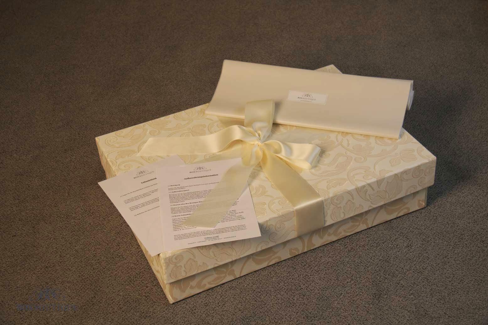 Die Brautkleidbox wird inkl. Satinschleife, säurefreiem Seidenpapier, Aufbewahrungsinformation und Faltanleitung geliefert.