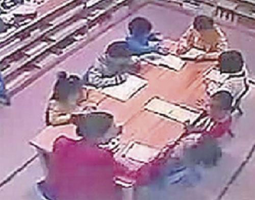 RAKAMAN video menunjukkan guru wanita (membelakangkan kamera) menampar seorang daripada muridnya.