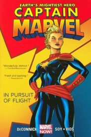 Cover of Captain Marvel Volume One, featuring a white woman with short blonde hair. She wears a formfitting blue and red flight suit with an eight-pointed yellow star over on her chest and strikes a heroic pose, hands on hips, against a background that matches her costume.