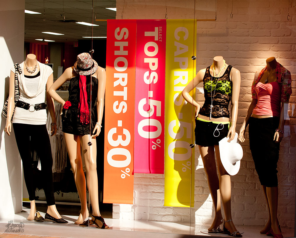 A sale sign and chic mannequins in a trendy clothing shop at the Orillia square Mall.