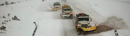 photo of three large snow plowers clearing a highway after heavy snow