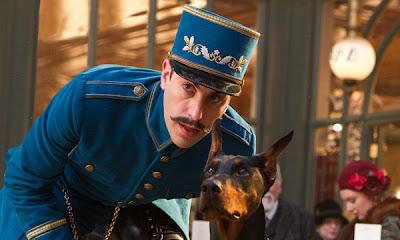 Fotograma de La invención de Hugo con Sacha Baron Cohen como el inspector de la estación con su perro Maximilian (Blackie)