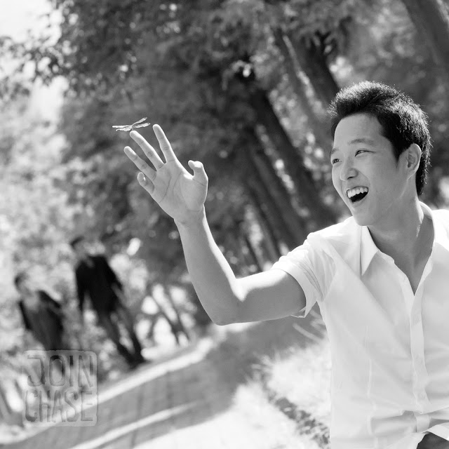 A young Korean man in a park in South Korea with a dragonfly on his hand.