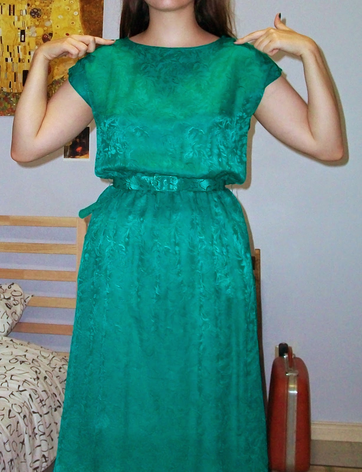 Photo of woman in green dress pointing at her shoulders.