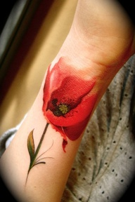 Red faded rose tattoo on wrist