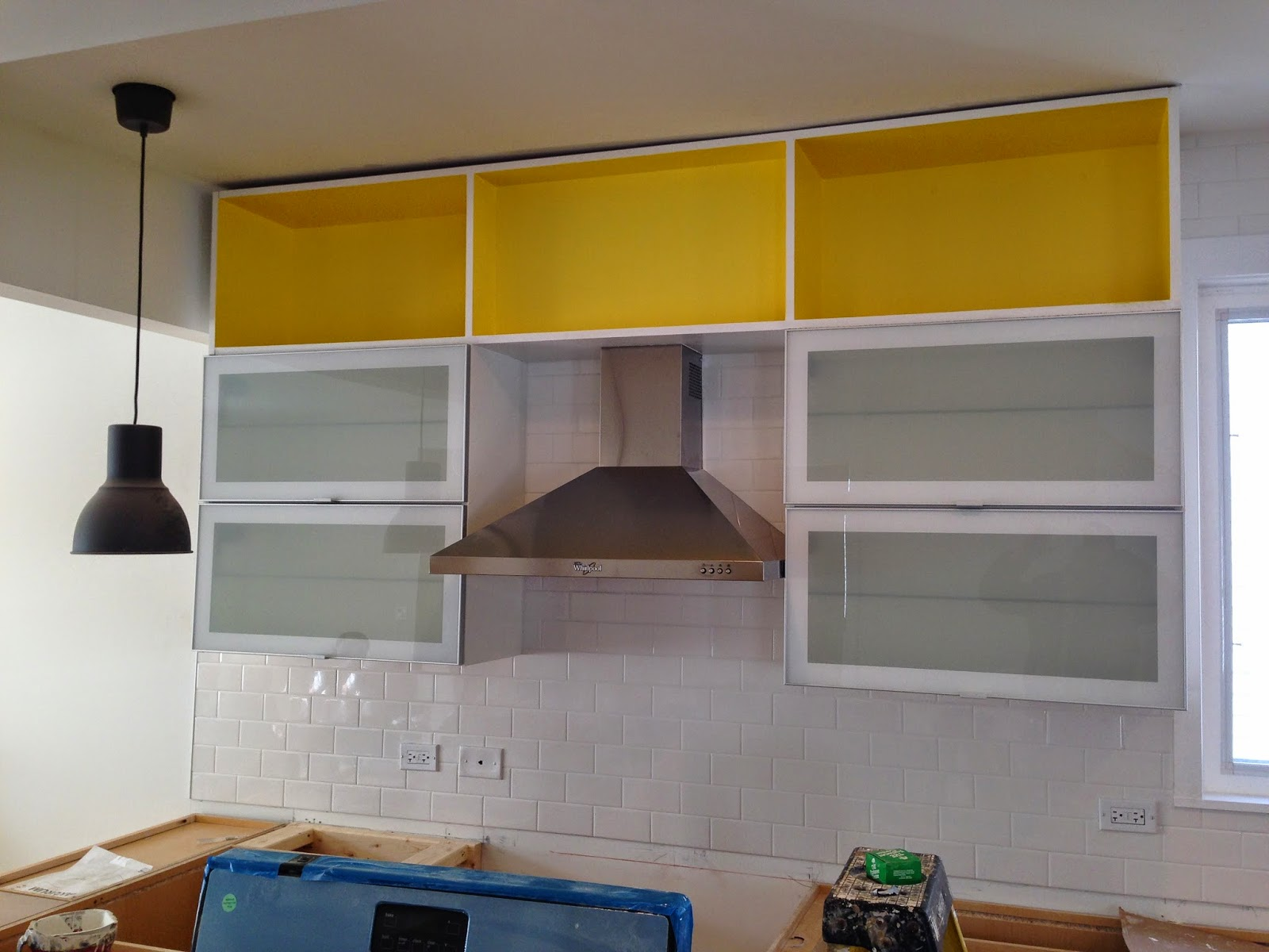 the open kitchen has maple base cabinets glass wall cabinets
