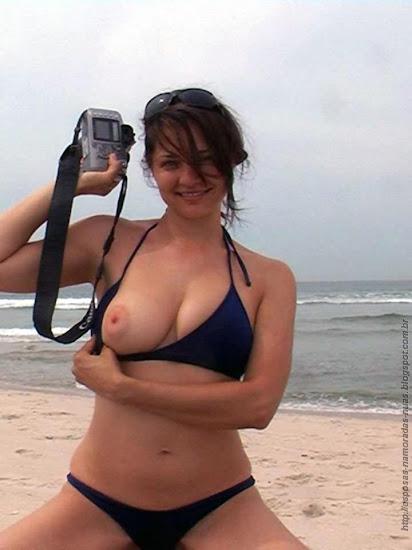 menina de auréolas grandes mostrando um peito na praia