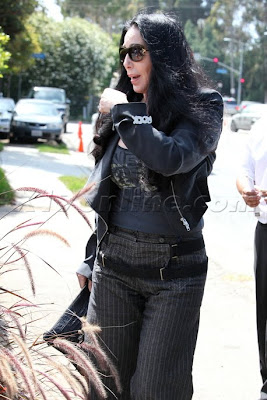 Cher wearing a brooch with the word 'Rock' on it