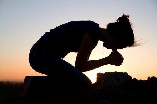 woman praying on her knees