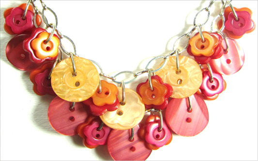 Cool necklace has orange and red fashion buttons layered on silver chain