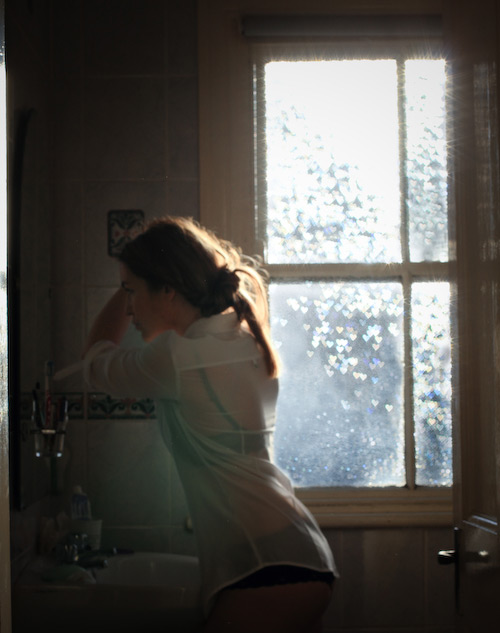 Woman fixing her hair at the bathroom mirror in the morning light