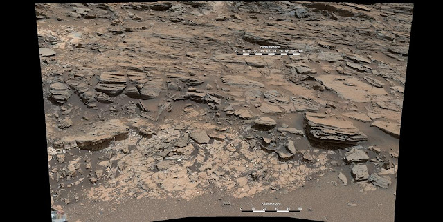 "This May 25, 2015, view from the Curiosity rover's Mastcam shows a site where two different types of bedrock meet near ""Marias Pass"" on Mount Sharp. Pale mudstone in the foreground is like bedrock the rover studied at ""Pahrump Hills."" The darker sandstone above it is called the Stimson unit. Credits: NASA/JPL-Caltech/MSSS"