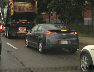 garbage truck followed by a Chevy Volt on a road in traffic