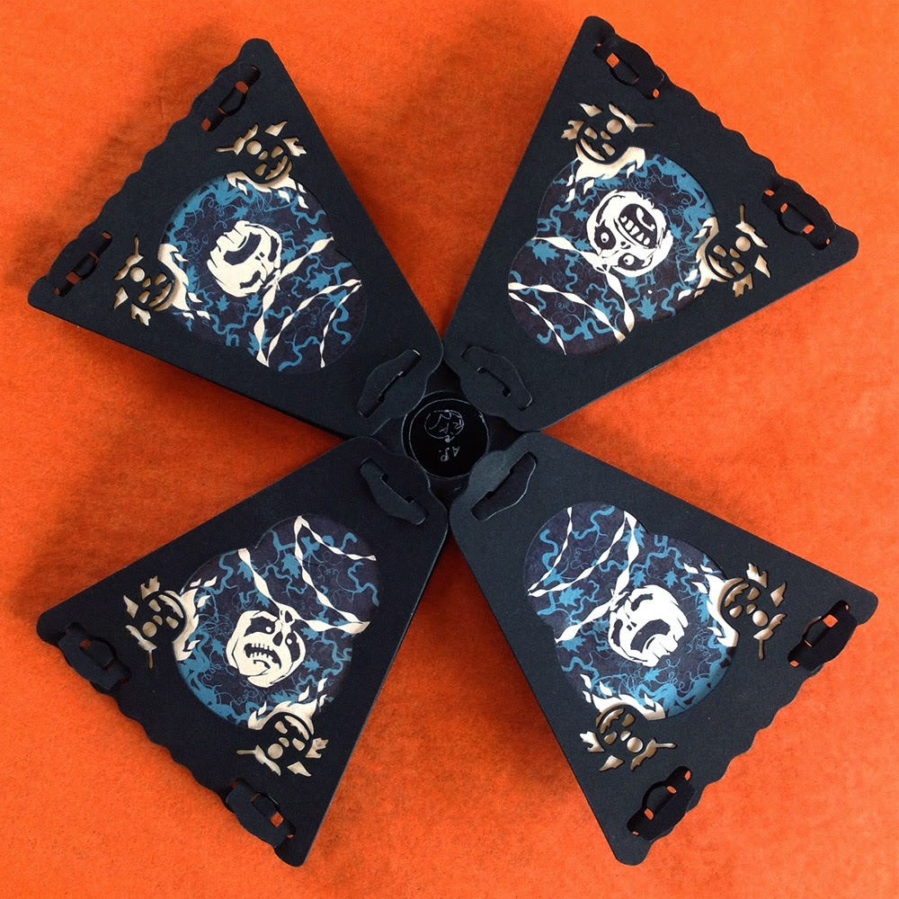Eight-sided paper lanterns feature pattern of pumpkins, crepe streamers, and vine leaf motifs in blue and black Halloween