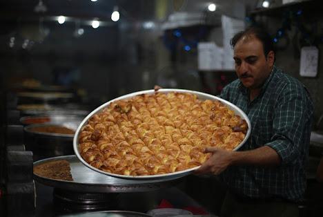 Seorang koki memegang nampan kue Arab