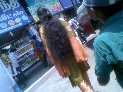 South Indian young girl with long hair shopping at market street.