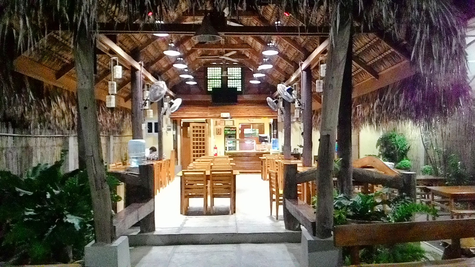 A long nipa hut houses the dining area of this restaurant wooden tables and chairs inside and outside the hut are available for customers