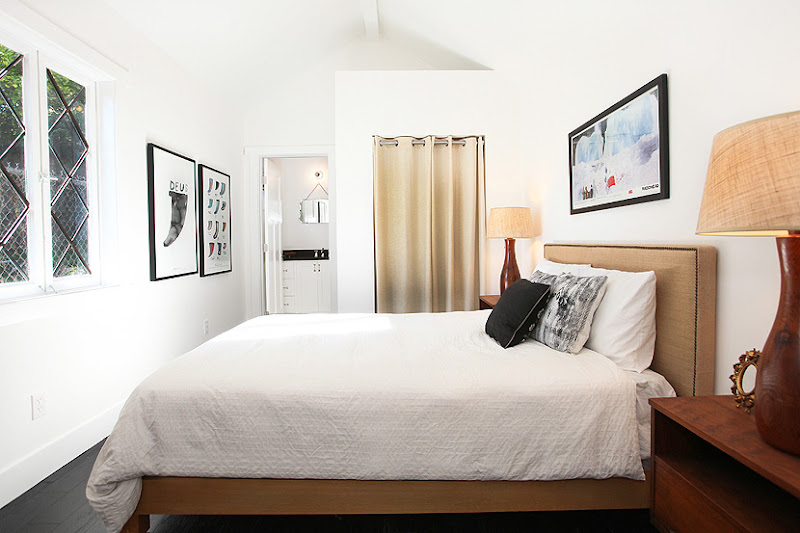 Guest bedroom in a cottage with diamond encasment windows, a tan upholstered headboard, a wood nightstand, stained wood floor and art in black frames