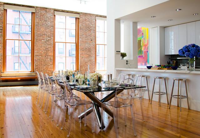 mesa com pernas cruzadas, cadeiras ghost, cadeiras de acrílico, parede de tijolos à vista