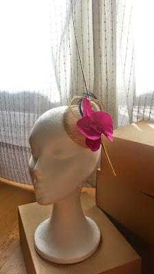 Tocado con orquídea artesanal color cardenal, base de sinamay con hilo metálico decorada con raqui de avestruz color dorado y plumas de oca