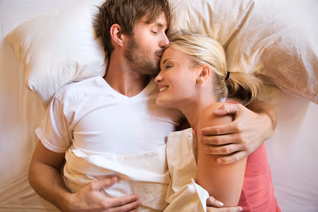 Couple turning towards each other and embracing in bed.