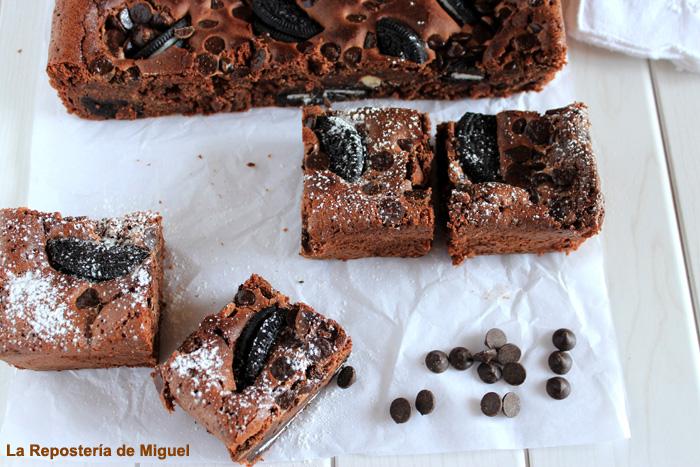Porciones de brownie cortadas cuadradas y de decoración pepitas de chocolate sobre papel de horno. Todo ello sobre una mesa de madera blanca