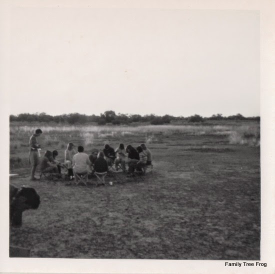 Group of children sitting in circle having dinner at dusk on camp stools