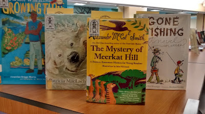 Books arranged upright, front covers facing forward, in a row on a countertop. From left to right, they are 'Farmer Will Allen and the Growing Table' by Jacqueline Briggs Martin, 'White Fur Flying' by Patricia MacLachlan, 'The Mystery of Meerkat Hill' by Alexander McCall Smith and 'Gone Fishing' by Tamera Wissinger