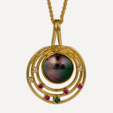 black flat pearl surrounded by concentric rings, white, pink and green stones