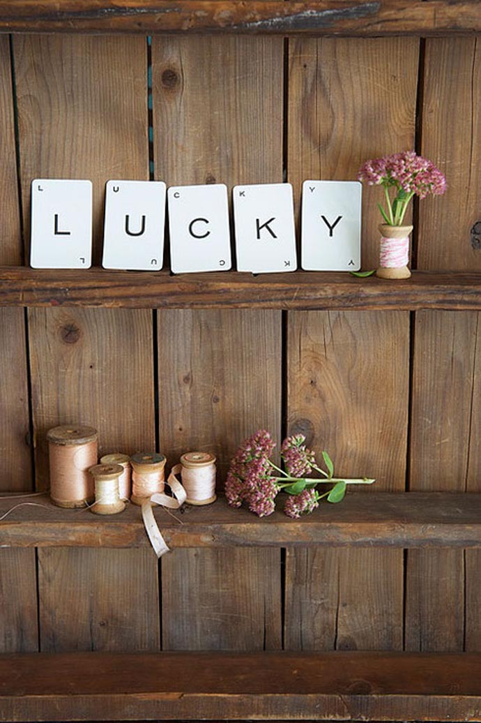 Cards spelling LUCKY on a wooden shelf with flowers next to them